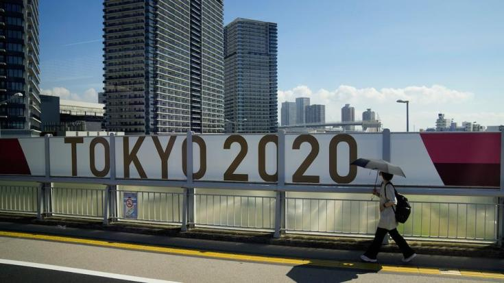 A woman walks on a bridge past a Tokyo 2020 banner ahead of the 2020 Summer Olympics, Saturday, July 17, 2021, in Tokyo.