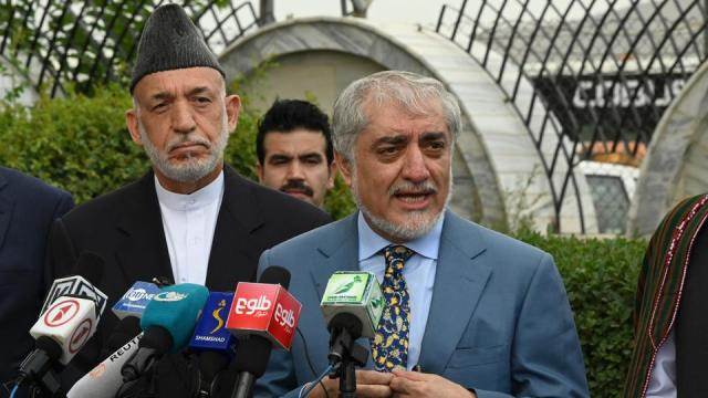 Chairman of the High Council for National Reconciliation Abdullah Abdullah (C) speaks next to former Afghan President Hamid Karzai (L) during a press conference at Hamid Karzai International Airport in Kabul on July 16, 2021.