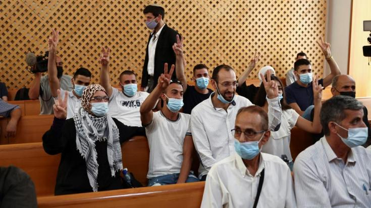 Members of the El Kurd family, Palestinian residents of Sheikh Jarrah neighbourhood in occupied East Jerusalem who are facing eviction, and a supporter of the family, flash victory signs during a court hearing, in the Israeli Supreme Court, in Jerusalem, August 2, 2021.