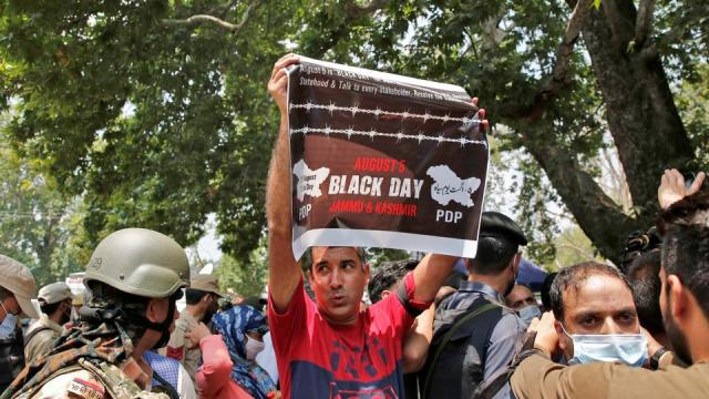 A supporter of the Peoples Democratic Party holds up a poster during a protest demanding the restoration of Kashmir's autonomy, in Srinagar on August 5, 2021.