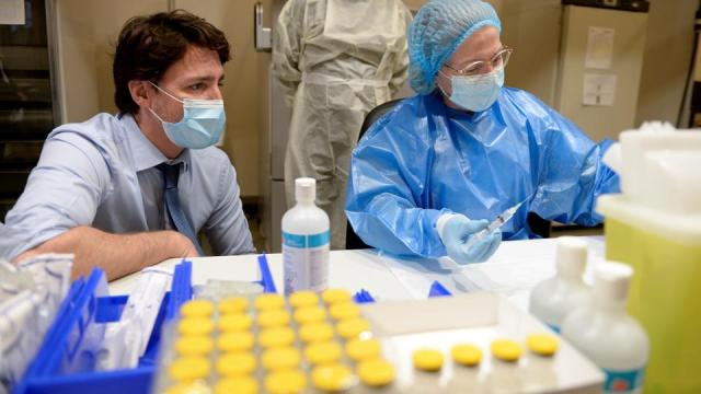 Canada's Prime Minister Justin Trudeau watches the Pfizer-BioNTech vaccine being extracted while he visits a vaccination clinic at the Palais des Congres, in Montreal, Quebec, Canada, March 15, 2021.