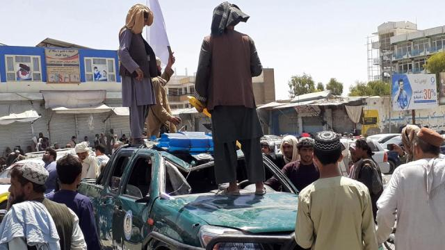 Taliban fighters stand over a damaged police vehicle along the roadside in Kandahar on August 13, 2021.
