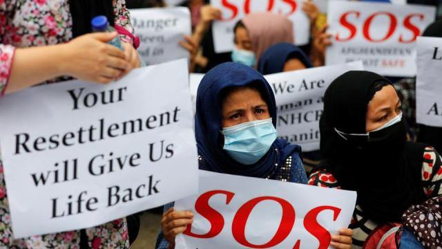 Afghan refugees holding placards ask for justice and resettlement during a rally outside the UN Refugee Agency UNHCR's office in Jakarta, Indonesia, August 24, 2021.