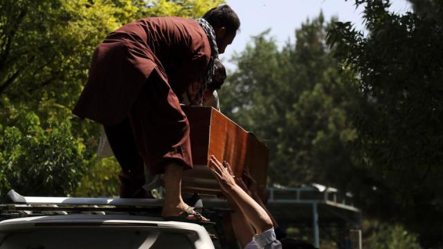 Afghans carry the dead body of an Afghan at a hospital in Kabul, Afghanistan on August 27, 2021.