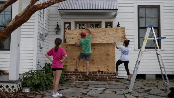 Sophia, 12, watches as her parents Christina and Jean Paul Bourg place plywood in front of an entrance to their home in preparation for Hurricane Ida in Morgan City, Louisiana, US, on August 28, 2021.