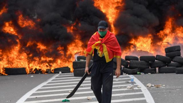 A man walks past burning tyres s at a barricade set up to block access roads to the historic city of Cetinje on September 5, 2021 in Montenegro.