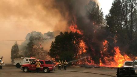 In this photo provided by the Cal Fire Communications, firefighters battle a wildfire in an area northeast of Clearlake Oaks, California, June 24, 2018