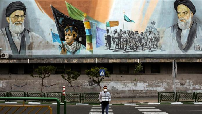 A man crosses an empty street under portraits of the late Iranian revolutionary founder Ayatollah Khomeini, right, and Supreme Leader Ayatollah Ali Khamenei, left, in Tehran, Iran, on April 3, 2020.