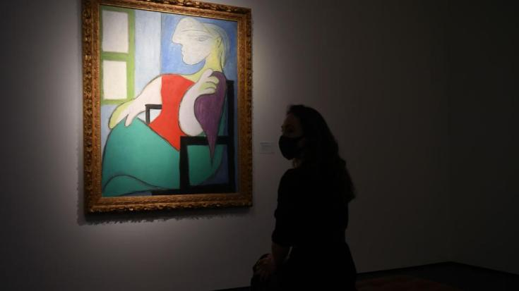 A gallery worker poses alongside an artwork titled 'Femme assise près d'une fenêtre (Marie-Thérèse)' by Spanish painter Pablo Picasso during a photocall at Christie's auction house in central London on April 22, 2021.