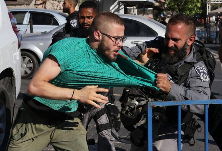 A member of Israeli security forces grabbed Palestinian man during scuffles in the Old City of Jerusalem, ahead of the March of the Flags on  on June 15, 2021