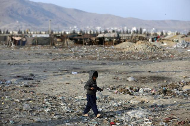 An internally displaced boy walks outside his temporary home in the city of Kabul, Afghanistan, Monday, Jan. 18, 2021.