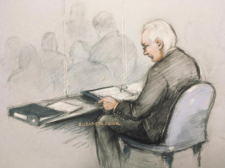A court artist sketch of Assange in the dock reading his papers as he appears at Belmarsh Magistrates' Court for his extradition hearing, in London, February 24, 2020. If extradited to the US, Assange faces up to 175 years in prison.
