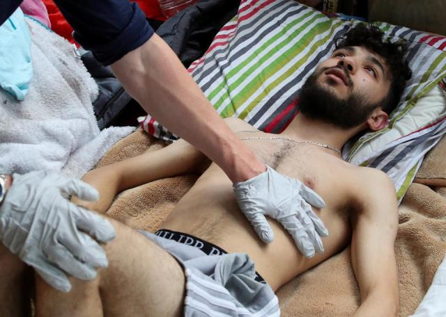 Moroccan Nassr Eddine Tssouli, 20, an asylum seeker who is among several hundred migrants requesting to be regularised by the Belgian government to have access to healthcare, is helped by a medic, as he takes part in a hunger strike for more than a month, at the campus of Belgium university ULB/VUB, in Brussels, Belgium July 6, 2021.