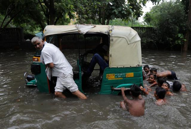 A man pulls his auto rickshaw through waterlogged street after heavy rains in New Delhi, India, July 27, 2021.