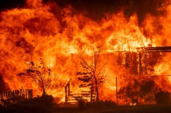 Flames consume a home as the River Fire tears though Lakeport, California., on Tuesday, July 31, 2018.