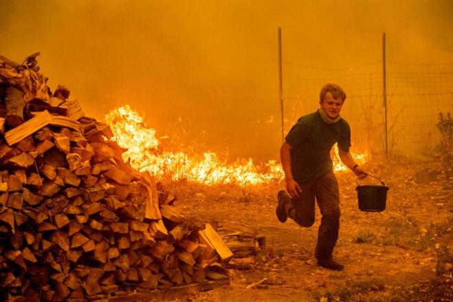 Alex Schenck carries a water bucket while fighting to save his home as the Ranch Fire tears down New Long Valley Rd near Clearlake Oaks, California, on Saturday, August 4, 2018. The Ranch Fire is part of the Mendocino Complex, which is made up of two blazes, the River Fire and the Ranch Fire.
