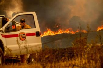 The Ranch Fire, part of the Mendocino Complex Fire, crests a ridge as Battalion Chief Matt Sully directs firefighting operations on High Valley Rd. near Clearlake Oaks, California, on Sunday.