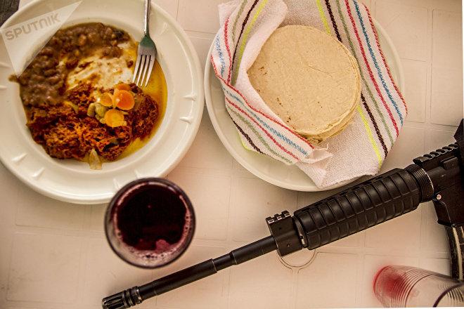 Michoacán. Armas en la mesa de la comida de las autodefensas michoacanas.