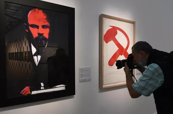 A lo largo de la década de 1970 y hasta su muerte en febrero de 1987 a raíz de una inesperada arritmia post-operatoria, Warhol siguió produciendo imágenes que representaban a celebridades políticas y de Hollywood, además de crear una amplia gama de ilustraciones publicitarias y participar de otros proyectos de arte comercial.En la foto: un fotógrafo toma instantáneas de unas obras de Andy Warhol durante una exposición del trabajo del artista en Moscú. - Sputnik Mundo