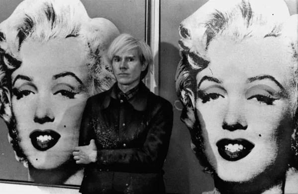 El año siguiente, pasó a utilizar la técnica de serigrafía fotográfica para producir en masa estas imágenes deliberadamente banales de bienes de consumo. A la vez, comenzó a imprimir numerosas variaciones de retratos de celebridades en colores llamativos, siendo su representación de Marylin Monroe quizás el más conocido de ellos.En la foto: Andy Warhol posa delante del retrato de la fallecida actriz Marilyn Monroe, en la Galería Tate de Londres, el 15 de febrero de 1971. - Sputnik Mundo