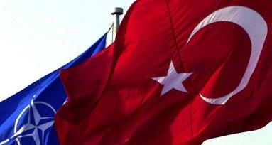Una bandera turca enfrente de una de la OTAN