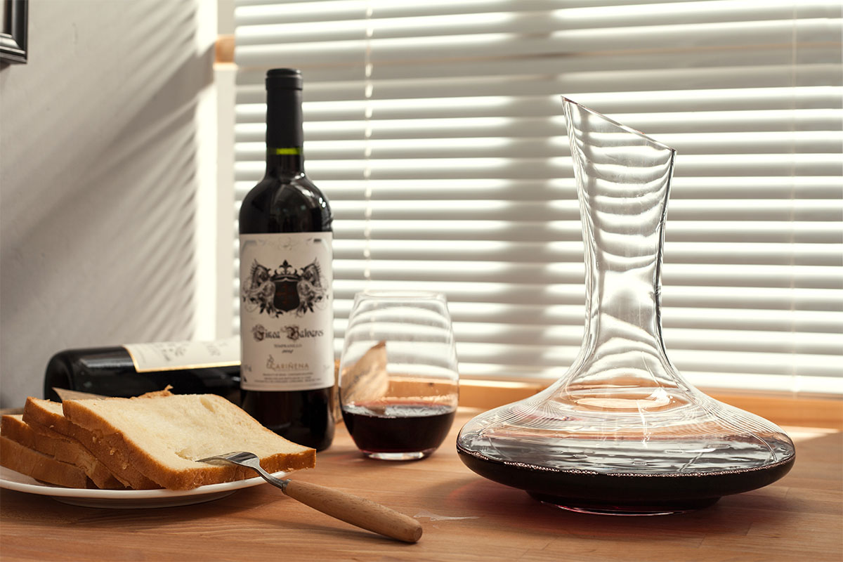 A decanter, wine and bread on a tabletop