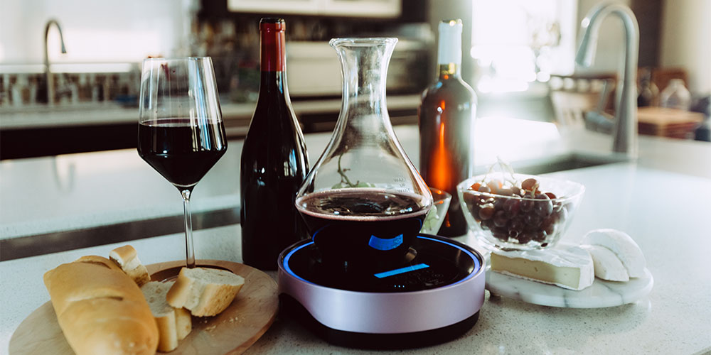 A countertop with an electric decanter, wine, cheese, fruit and bread