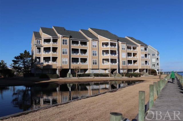 """A blank canvas ready to be made into your perfect home, this 2 Bedroom, 2 Bath condo with a elevator and amazing views in the Outer Banks premier boaters community of Pirates Cove - Buccaneer Village. Open living area with sound, pond and canal views.  A spacious deck back and front allows for enjoying outdoor breezes and water views from both and amazing sunsets from the front deck. Large storage ground floor lockup for all your beach toys. A qualified boat owning buyer will have rights to a 25 ft boat dock slip for $130 a year. More than just a home, Pirates Cove is a lifestyle. """"Fishing, fun and friends"""". Enjoy access to world class fishing and water sports. Association amenities include swimming pools, clubhouse, fire pit, volleyball, basketball, pavilion, fitness center, marina that has over 4 miles of docks that are fantastic for walking or running, or just kick back and watch the boats come in from your deck or relaxing at the marina restaurant. Don't have a boat? No problem charter or walk just under the bridge to the NC Wildlife water access including fishing pier, boat ramp and multiple launch sites for small craft kayaks etc. This home allows for quiet enjoyment, while being walking distance to the fun."""