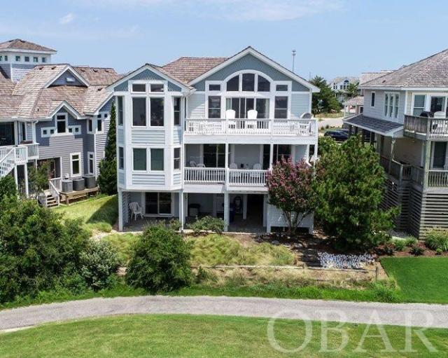 Beautiful panoramic water and golf views. Conveniently located near Grocery stores, outlet shopping, fishing piers and great restaurants. A bike path and walking trail extends for miles. Two sound side parks and piers for your enjoyment. This Outer Banks home in Nags Head, offers views of the 18th and 17th fairway of Nags Head golf links, sound views and sunsets that will take your breath away. Enjoy from covered decks or sundecks with Trex decking.  A private elevator takes you to all three floors.  A spacious living area with open dining kitchen and great room and a master bedroom with a handicap friendly bath and half bath on the top level.  A den on the second floor allows you room to enjoy a book or a movie, the sound-side grand master and two other large bedrooms.  The first floor has a Dry entry and ground floor master,  The outside living areas include spacious decks, a patio, a fish station and a outdoor shower, there are two large storage areas for all your tools and beach toys.   A beach and tennis Club with a massive pool, children's pool bath houses, game area, showers and club house and Nags Head Golf Links memberships are available. Use all or as little of the amenities offered in the Village and only pay for what you chose to use. Free shuttle for you and your guest, sound side parks and piers and beach access and bath house are there for all owners and guest. Beach club and golf links are private membership. A short trip to Jockeys ridge or the Oregon Inlet Fishing center and more.