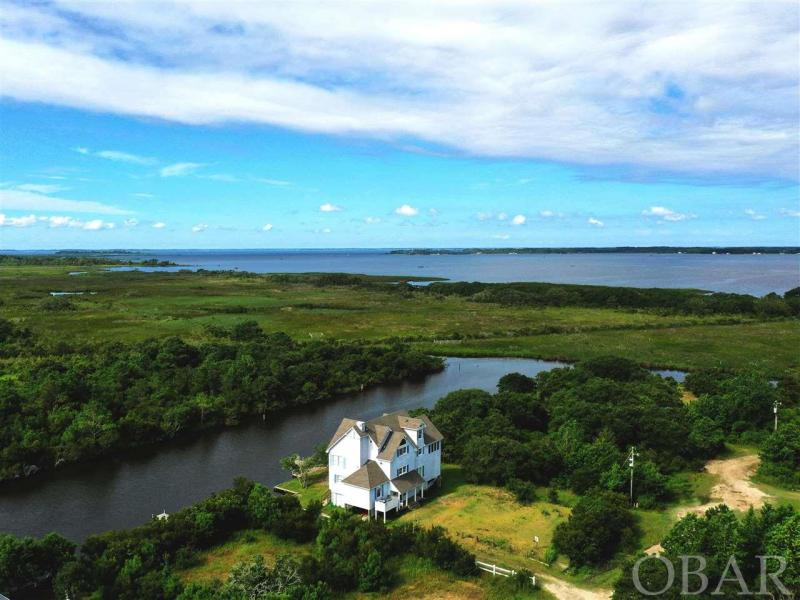 Large 5 bedroom house on a canal overlooking the marsh & sound! Recent renovations include updated windows fresh pain inside as well has other little details. With Fish & Game land across the canal to the South and the Sound out to the West this location is a rare find in Carova offering of the most BEAUTIFUL and PRIVATE views in Carova.  The house offers 4 bedrooms on the lower level with one master suite, a large living space on the upper level with a roomy screened in porch and decks leading down to the back yard & boat dock, and then on the top level you have a private suite offering the best views in the whole house!