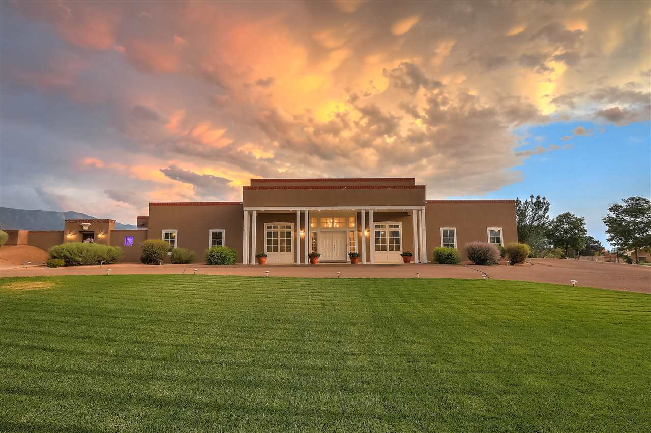 Beautiful NM Territorial designed home by Claudio Vigil. Extremely light and bright with large rooms and open floor plan. 14 foot ceilings and 9 foot doors. Radiant heat and refrigerated air. Master is separated from other 3 bedrooms and provides a refuge complete with a fireplace, luxurious master bath and attached exercise room or study with access to back courtyard. Tile floor and carpet throughout. The back courtyard has spectacular views of the Sandias and a large tiled fountain. There is a self contained in law or teen guest house with kitchenette, bath, and living room and bedroom that is entered from the courtyard or the 4 car garage. Privacy abounds in this beautiful home, make it your own!