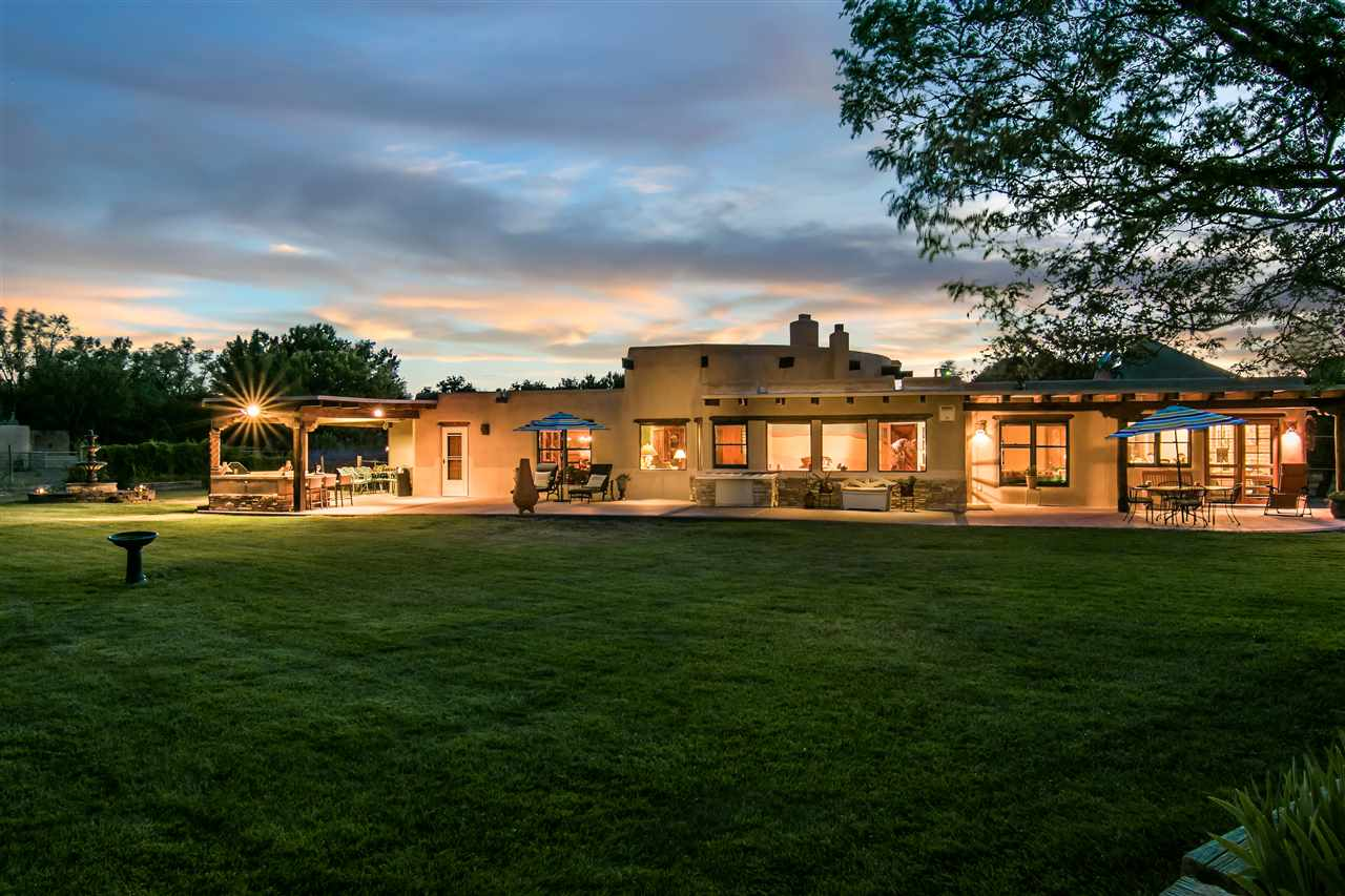 This unique home is sure to please from the amazing interior adobe walls and bancos to the beautifully designed Al Knight Kiva fireplaces. The Master Suite boasts 2 walk in closets, an over-sized dressing room or office with an outside entrance, Kiva fireplace and bonus hobby or sitting room. The 4th and 5th bedrooms are a perfect retreat for in-law or teenage quarters with a private entrance and pergola. Entertain with the outdoor kitchen and patio. Horse barn, arena, raised gardens, mature Fruit trees and riverbank access. Adjacent pasture land available for purchase.