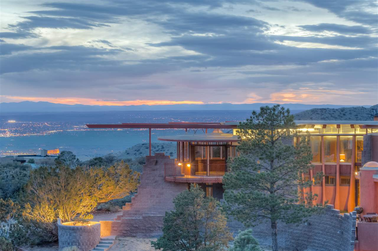 Award winning Bart Prince design in North Sandia Heights with FOREVER views. This home was designed & built for his father. A real labor of love! Multilevel plan with exposed beams, lots of light including skylights and full walls of windows. An architectural marvel. Terraces and decks on all sides joining the outside and inside spaces. Contemporary design, inside and out. Incredible architectural detail. Boulders used from site for the custom fireplace and left in place in the entry & MBR. Modern kitchen with granite counter tops. 2 bedrooms with Jack & Jill bathroom separated from Master. Kiva style office with windows all around. Outside wrap around patios for sunset & city light views and, in front, a view of the Sandia Mountains. Almost 1 acre lot bordering Open Space & 3 car garage.