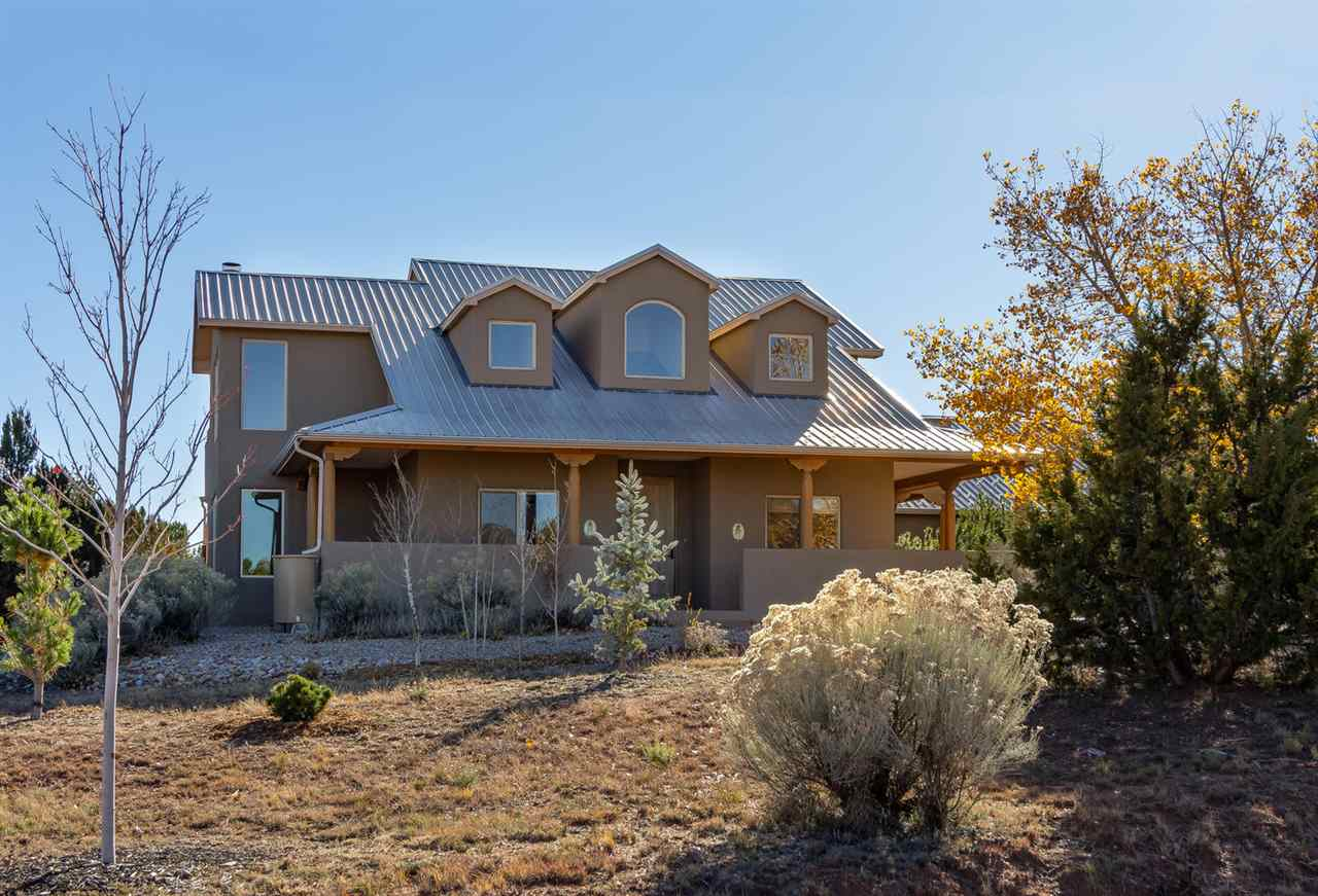 Awaken each day in spacious, sun-filled rooms to the sounds and sights of Nature in this beautifully loved and meticulously maintained, custom, Northern New Mexico-style home. Rocking-chair ready wrap-around porch. Raised ceilings. Open floor plan. Kiva FP. Mountain Views! Private owners suite including loft and star-gazing deck. Newer stucco, Breezaire cooler, gutters and rain barrels, Anderson windows and doors. Enjoy world-class golf, access to the Paa-ko event center, pool and tennis courts. See the joys that life has to offer at an amazing price!
