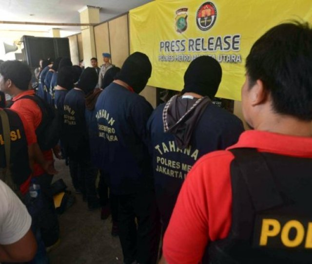 Indonesian Police Officers Stand Guard As Men Arrested In A Raid Are Being Shown To The Media During A Press Conference At A Police Station In Jakarta