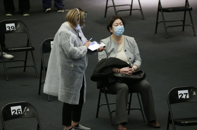 Healthcare workers attends to a woman in the observation area after being vaccinated at the American Museum of Natural History in New York City on Friday. Photo by John Angelillo/UPI