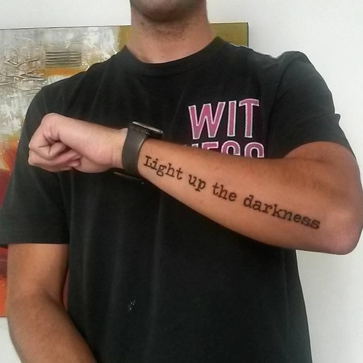 Tatuaje Que Dice Light Up The Darkness En El