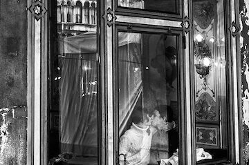 black and white photo of a couple kissing in a restaurant window