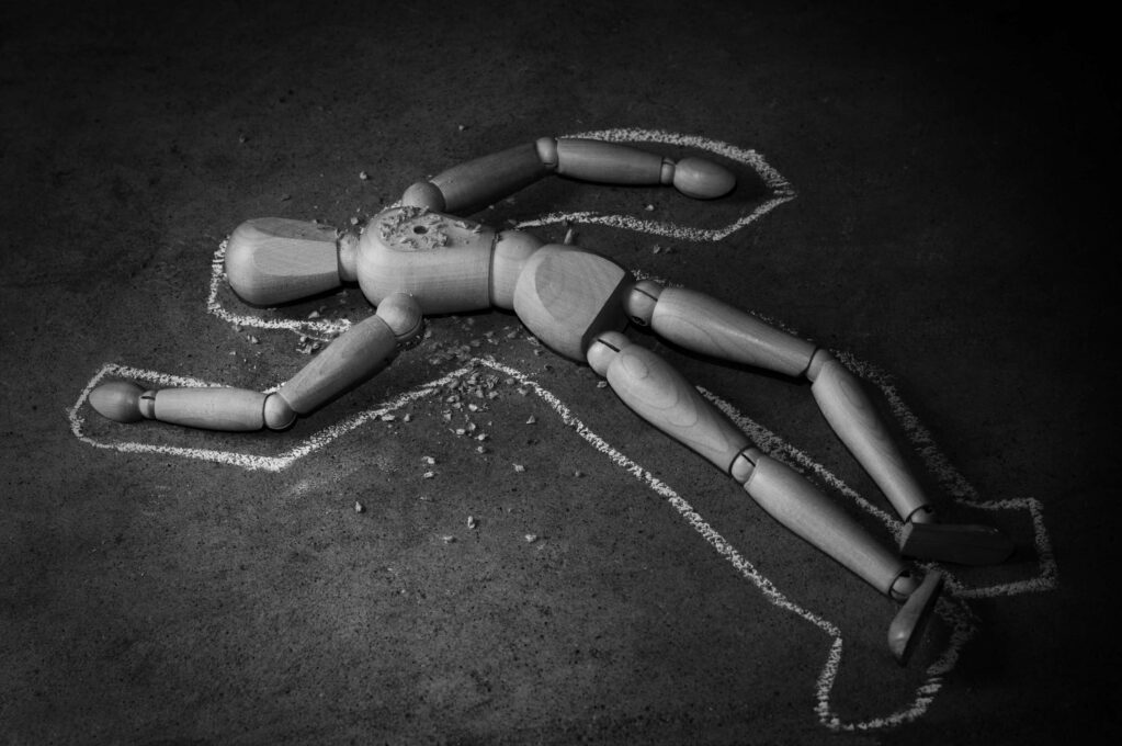 photo of wooden mannequin in chalk outline