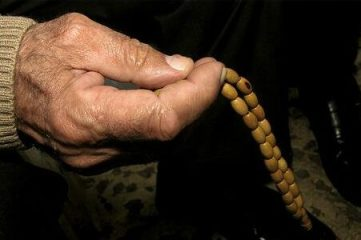 photo of a hand holding beaded necklace