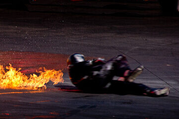 photo of a stuntman on ground near fire