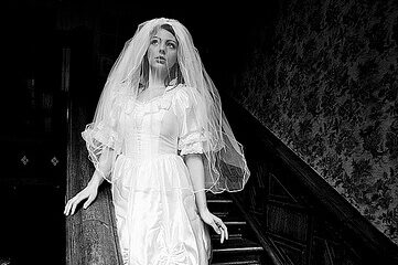 photo of woman in bridal gown posing on old staircase
