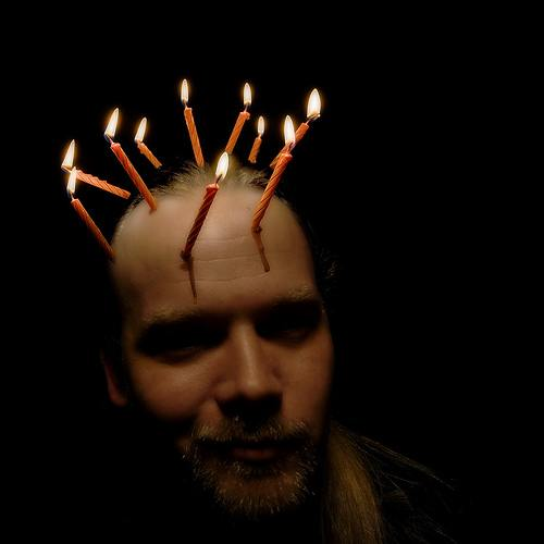 photo of man with lit candles attached to his head