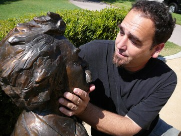 photo of man caressing the face of a Mark Twain statue