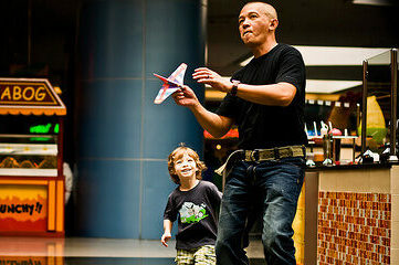 photo of man holding a toy plane in a mall with boy standing beside him