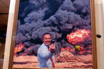 photo of a man taking a selfie in front of apocalyptic art piece on wall