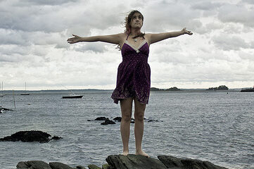 photo of a woman standing on a rocky beach