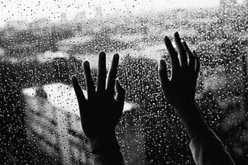 black and white photo of hands pressed up against the inside of a rainy window
