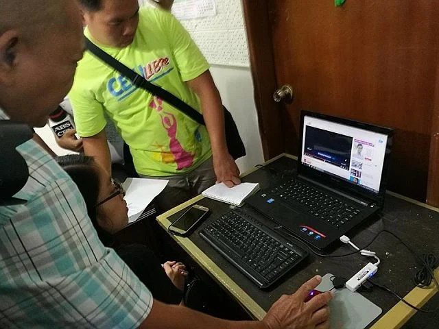 Woman wanted in Mindanao for human trafficking nabbed in Cebu NBI CEbu agents viewing the video of the molestation a baby girl, one of the evidences against a wanted human trafficker Liezyl Margallo, who was arrested in a resort on Malapascua Island on Wednesday. (CDN PHOTO/ CHRISTIAN MANINGO)