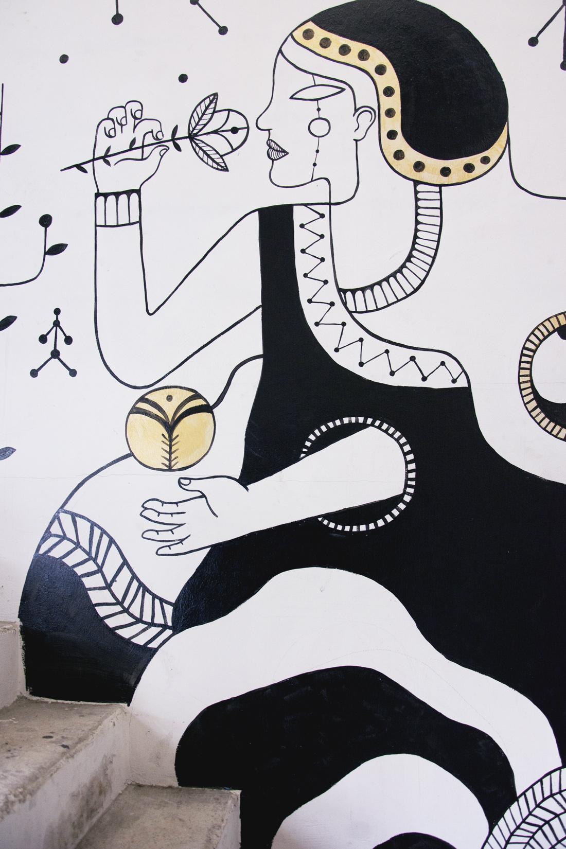 Fresque avec dessin de femme en noir et blanc tenant une fleur